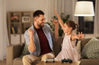 family, gaming and entertainment concept - happy father and little daughter with gamepads celebrating triumph in video game playing at home - 242665864