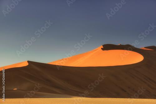 Sossusvlei salt pan with high red sand dunes in Namib desert, Namibia, Africa.