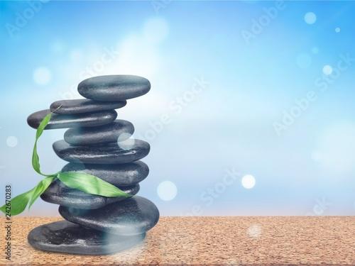 Leinwandbild Motiv Zen basalt stones and leaves on background