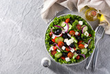 Fresh Greek salad in Plate with black olive,tomato,feta cheese, cucumber and onion on gray background. Top view. Copyspace - 242670850