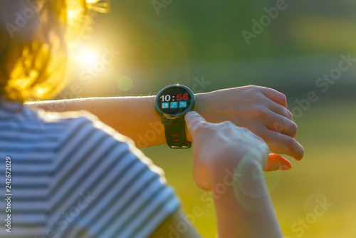 Woman using smartwatch with her finger