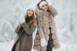 Portrait of two happy blonde women in hat on walk in winter forest