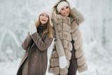 Portrait of two happy blonde women in hat on walk in winter forest - 242673085