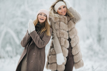 Portrait of two happy blonde women in hat on walk in winter forest