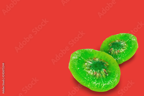 Pair of pieces of sliced dried green kiwi on red background with copy space for your text
