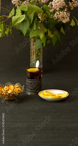 Still life with tea in a silver cup holder and bagels in a silver vase with lilac flowers on a black background