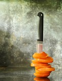 The orange is cut and stap by a old knife. on old glass desk in the kitchen room - 242694056