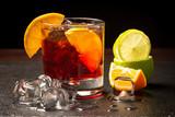 Cocktail rosso con ghiaccio e fette di limone in primo piano - 242694873