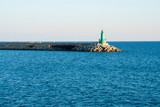 Small green lighthouse at the entrance of a port - 242695200