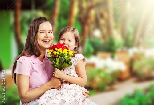 Foto Murales Young woman with little girl and beautiful flowers outdoors
