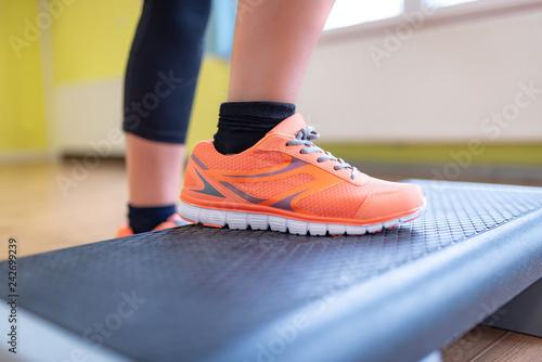 Leinwanddruck Bild Frau steht auf Steppbrett, Fitness, closeup