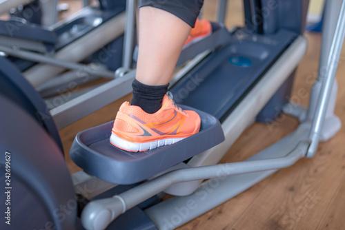 Leinwanddruck Bild Frau trainiert auf Crosstrainer, closeup