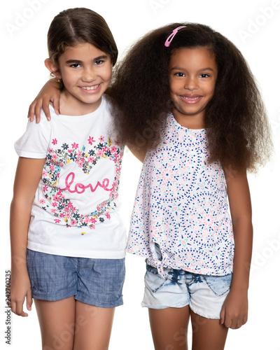 Cute hispanic and african-american small girls hugging