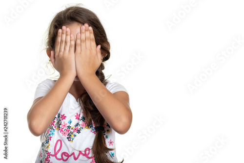Hispanic small girl covering her face with her hands