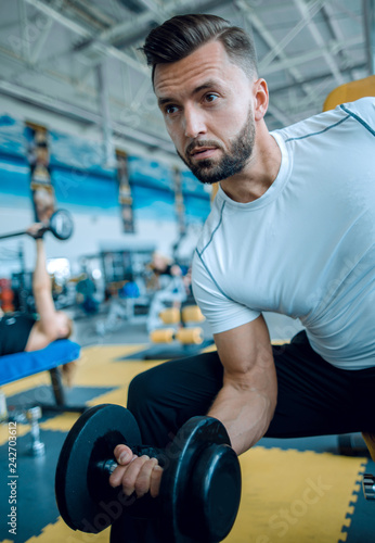 Leinwanddruck Bild Young male performing TRX training at the gym