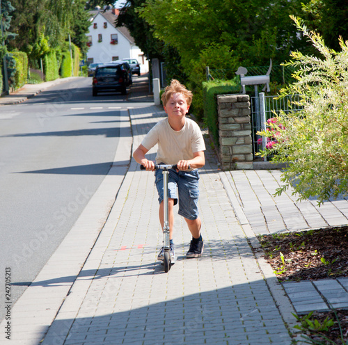 boy enjoys skating with his pust scooter at the sidewalk
