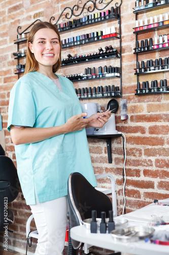 Leinwanddruck Bild Manicurist standing at her workplace in nail salon