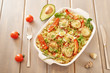 Pasta with pasta bows and vegetables, baked in the oven. Avocado, sweet peppers, cherry tomatoes and parmesan cheese in the dish. - 242709093