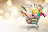 Variety office supplies in little shopping cart on wooden table - 242709484