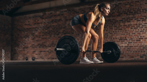 Poster Fitness woman performing weight lifting exercise at gym