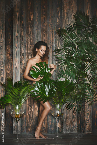 Beautiful and naked brunette model girl with blue eyes, with bright makeup and with the sexy body covers herself with leaves and posing among huge leaves of the plants at wooden interior - 242717081