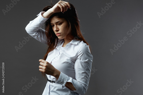 Gorgeous young woman dressed in white shirt with black belt stand on the dark gray background in the studio