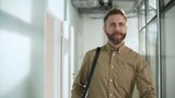 Dolly shot of successful businessman with beard walking confidently along office corridor and smiling when passing busy male colleague talking on phone - 242727480