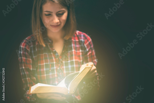 Young woman readin bible in a dark room