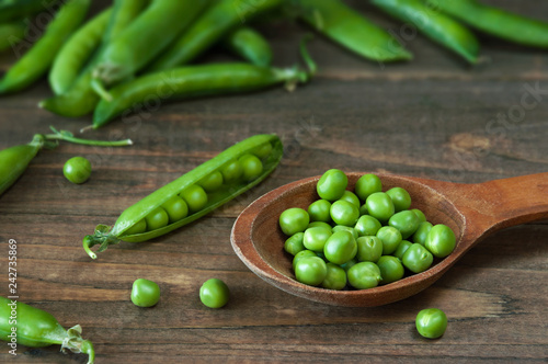 Fresh green peas in a wooden spoon on a table with pea pods.