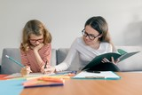 Young female teacher giving private lesson to child, little girl sitting at her desk writing in notebook