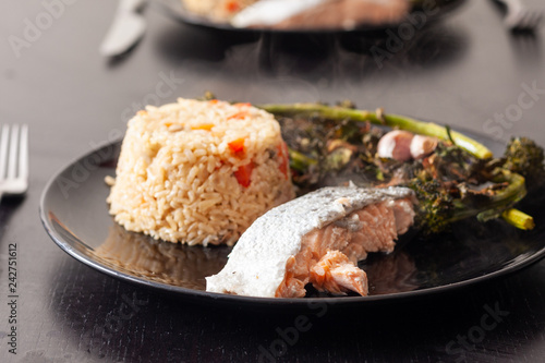 Salmon fillet served with brown rice and roasted tenderstem broccoli