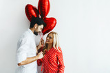 Couple. Love. Valentine's day. Emotions. Man is giving heart-shaped balloons to his woman, both smiling; on a white background - 242759851