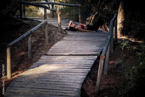 Mujer joven morena con el pelo suelto tumbada en el camino del bosque - 242760481
