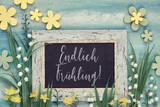 Spring background with text in German on a blackboard framed with spring flowers - 242761606