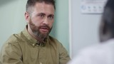 PAN shot of bearded businessman in casual shirt discussing work with unrecognizable man in meeting - 242762449