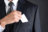 Businessman putting a blank business card into his jackets breast pocket - 242768824