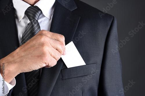 Leinwandbild Motiv Businessman putting a blank business card into his jackets breast pocket