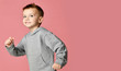 Leinwandbild Motiv Young baby boy kid in grey hoodie with free text copy space running happy smiling on pink