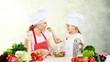 Leinwanddruck Bild - Cute little girl with vegetables in kitchen
