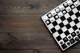 Chess game concept. Chess board with figures on dark wooden background top view copy space