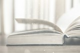 Open old book on wooden tabler on blurred background - 242787055