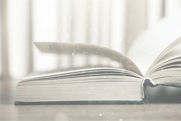 Open old book on wooden tabler on blurred background