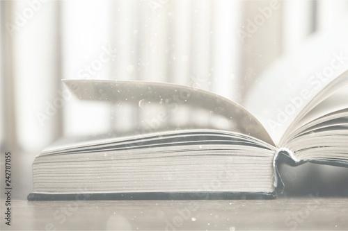 Leinwandbild Motiv Open old book on wooden tabler on blurred background