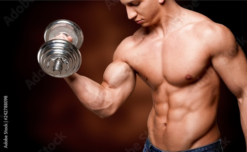Portrait of a handsome muscle man with dumbbell posing isolated