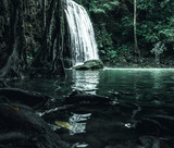 view of a beautiful waterfall in Thailand in a green jungle and clean environment in a moody green tone look surrounded with big trees and clear fresh green water which suggests an eco environment