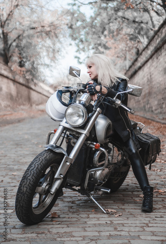 Beautiful biker woman outdoor with motorcycle.