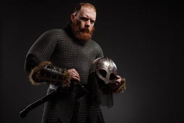 Warrior Viking in full arms with axe and helmet on dark background © Fotokvadrat