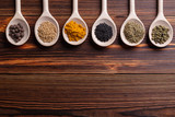 Mixed spices and herbs on wooden spoons with copy space. - 242810870