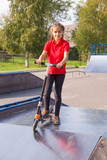 Portrait of cute young girl riding on a cick scooter in skatepark