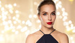 people, luxury and beauty concept - close up of beautiful woman in black with red lipstick over beige background and festive lights